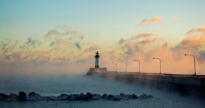 Sea smoke rises from Lake Superior over the North Breakwater Lighthouse during sunrise Friday, December 6, 2013 near Canal Park in Duluth, Minn.